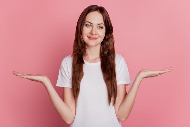 Retrato do assessor promotor com as palmas das mãos segurando um espaço vazio comparar no fundo rosa