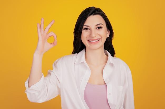 Retrato do assessor promotor menina positiva mostrar ok aprovar sinal em fundo amarelo