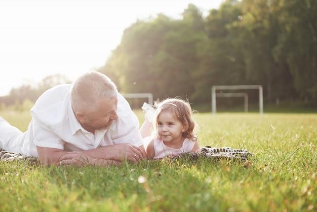 Retrato do avô com neta, relaxando juntos no parque