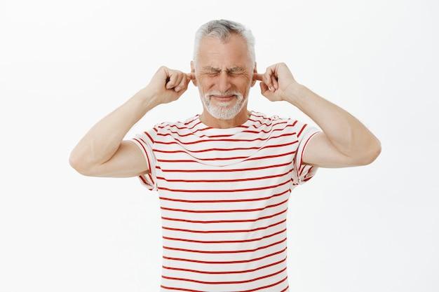 Retrato do avô descontente fechando os ouvidos com os dedos e fazendo caretas devido ao barulho alto