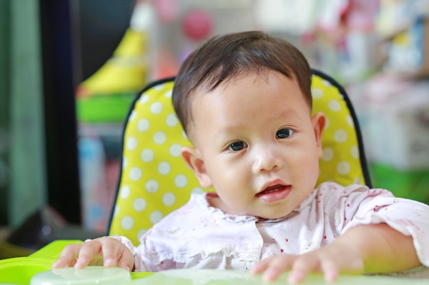 Retrato do bebê asiático pequeno de sorriso com o nariz ralo do ranho. close-up.