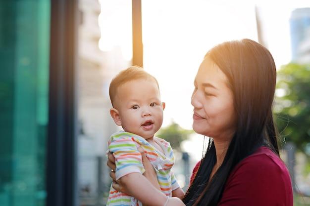 Retrato do bebê asiático que encontra-se no abraço da mãe com vista da câmera.