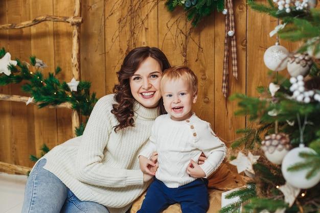 Retrato do bebê feliz da mãe e do filho. decorações de natal