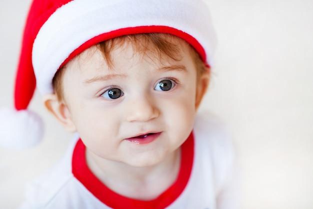 Retrato do bebê pequeno bonito de santa nos pijamas brancos e verdes. árvore de natal e presentes de ano novo no