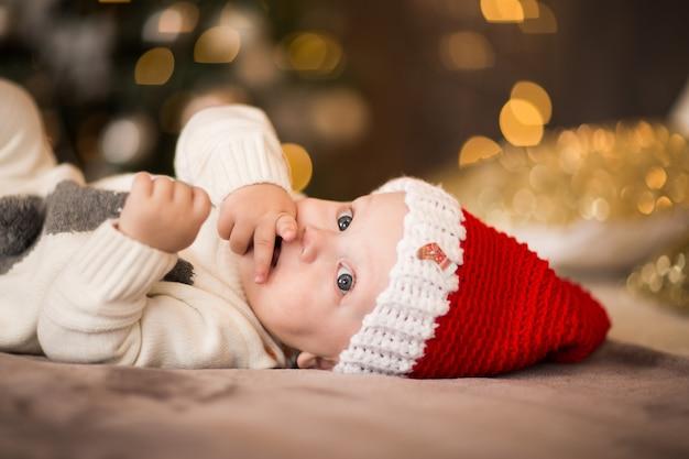 Retrato do bebê pequeno no tampão vermelho de santa que coloca em uma cama contra luzes de natal.
