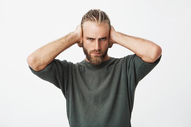 Retrato do belo barbudo nórdico, fechando os ouvidos com as mãos