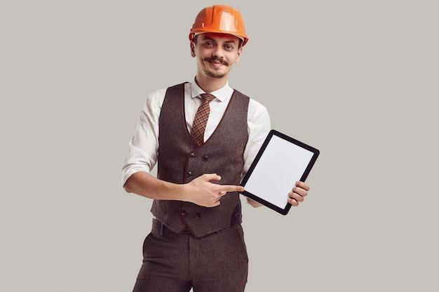 Retrato do belo jovem arquiteto árabe confiante com bigode chique no capacete de lã terno e construção detém tablet