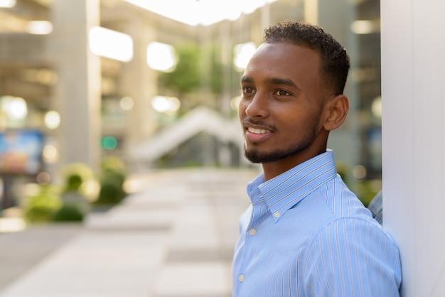 Retrato do bonito empresário negro africano ao ar livre na cidade durante o verão, sorrindo e pensando