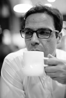 Retrato do bonito empresário persa relaxando na cafeteria em preto e branco