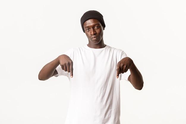 Retrato do cara afro-americano sério no gorro, olhando para a câmera e apontando o dedo para baixo com uma cara de pôquer