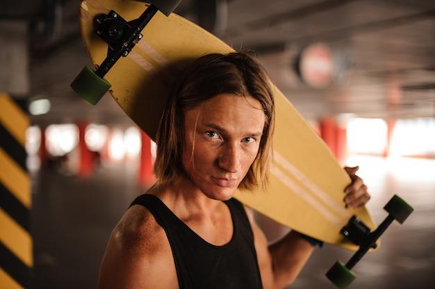 Retrato do cara atraente ruiva com um longboard