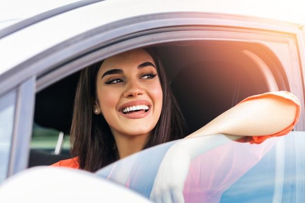 Retrato do carro de direção feliz motorista do sexo feminino com cinto de segurança.