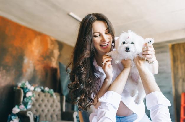 Retrato do casal casado e grávido alegre com um cão que encontra-se na cama na manhã.