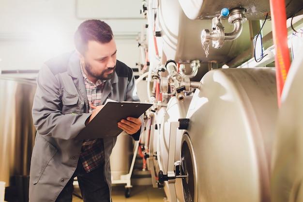 Retrato do cervejeiro que está fazendo cerveja no seu local de trabalho na cervejaria.