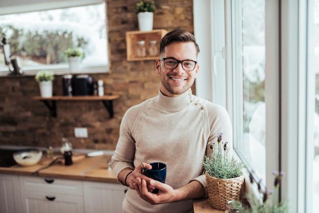 Retrato do chá bebendo do homem millenial de sorriso perto da janela na casa acolhedor na manhã do inverno.