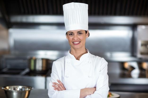 Retrato do chef feminino sorridente em pé na cozinha