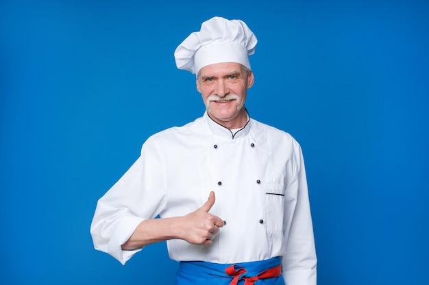 Retrato do chef idoso isolado na parede azul, com gesto de ok