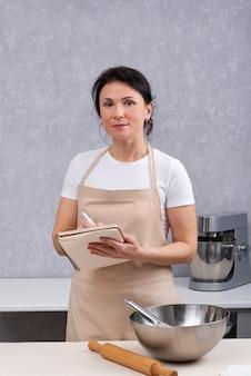 Retrato do chef mulher na cozinha com um livro de receitas nas mãos, ao lado da tigela e do rolo. quadro vertical.