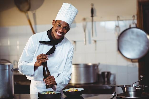 Retrato do chef polvilhar pimenta em uma refeição