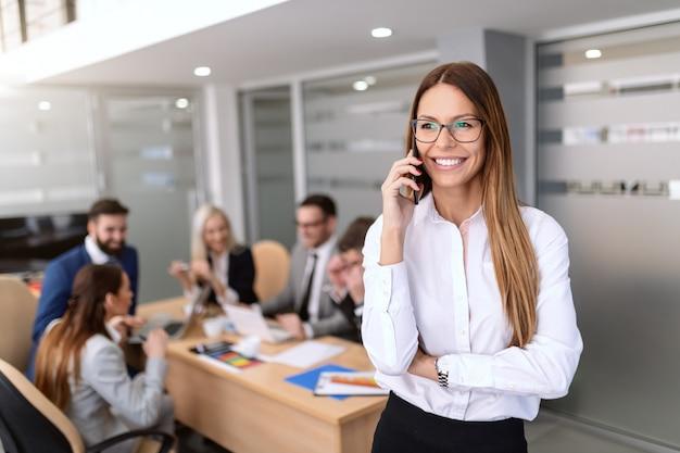 Retrato do chefe feminino sorrindo vestido com roupa formal e usando um telefone inteligente em pé na sala de reuniões