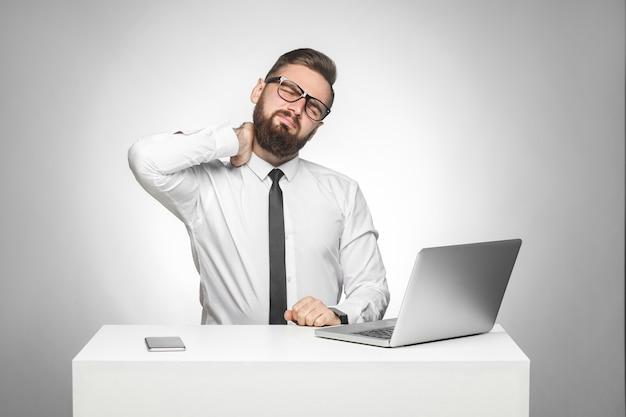 Retrato do chefe jovem cansado chateado não curado de camisa branca e gravata preta está sentado no escritório e tem forte dor no pescoço, segurando a mão no pescoço. foto de estúdio, isolada, fundo cinza, interior