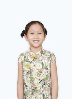 Retrato do cheongsam vestindo da menina asiática pequena feliz com sorriso. feliz ano novo chinês.