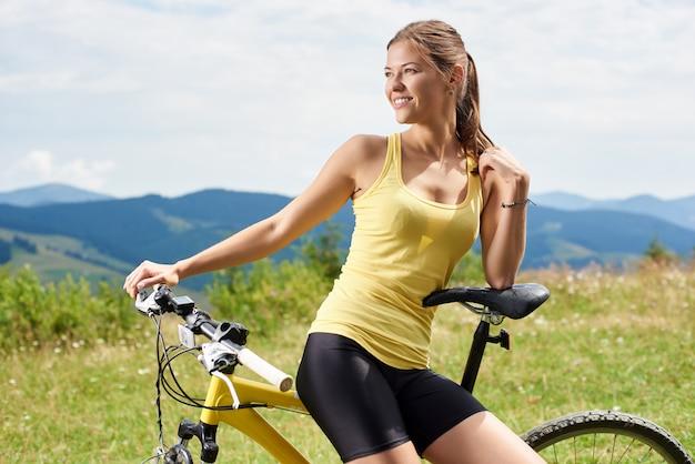 Retrato do ciclista feminino de garota atleta sentado na bicicleta de montanha amarela, aproveitando o dia de verão nas montanhas. atividade de esporte ao ar livre, conceito de estilo de vida