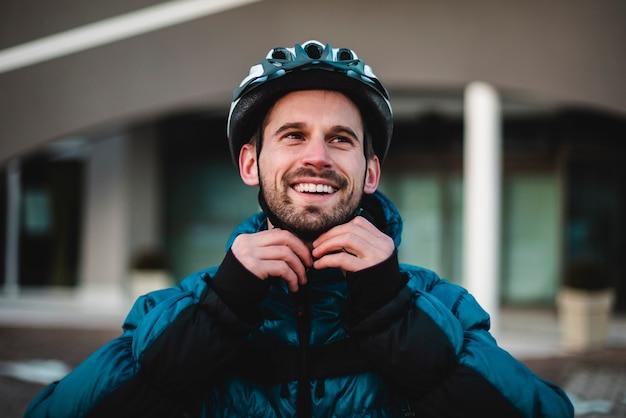 Retrato do ciclista prendendo seu capacete protetor. jovem feliz se prepara para as entregas em casa. retrato, ciclista, entrega em domicílio