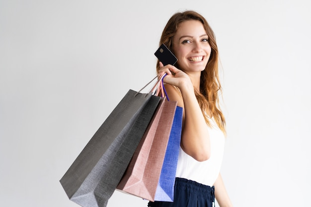 Retrato do cliente feliz com sacos de compras e cartão de crédito.
