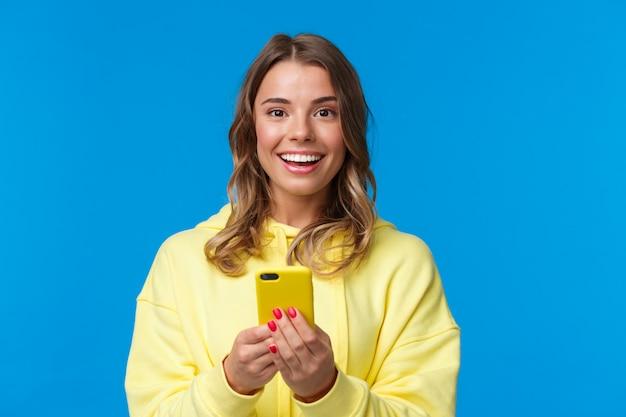 Retrato do close-up animado feminino europeu bonito sorridente com corte de cabelo loiro, segurando o telefone móvel e olhando a câmera entretida, mensagens de pé, conversando com amigos on-line