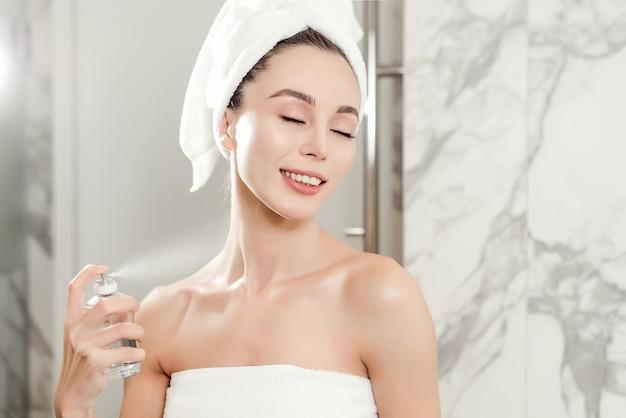 Retrato do close up com o perfume que pulveriza no pescoço da mulher bonita nova envolvida nas toalhas no banheiro. conceito de maquiagem e skincare de beleza