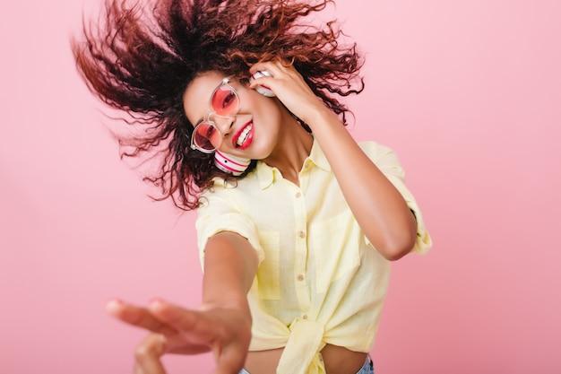 Retrato do close-up da adorável garota encaracolada feliz sorrindo. deslumbrante mulher africana com pele castanha-clara relaxando em fones de ouvido e dança engraçada.