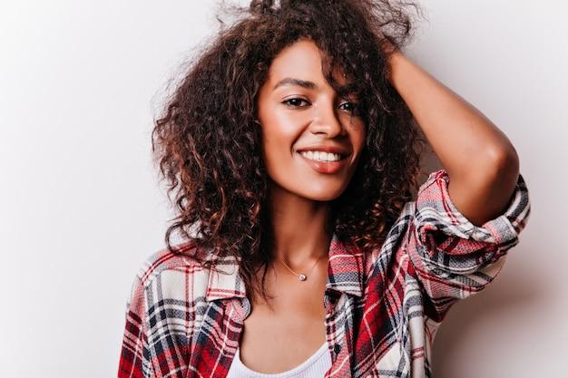 Retrato do close-up da adorável garota negra tocando seus cabelos ondulados. modelo feminino positivo usa a camisa quadriculada da moda.