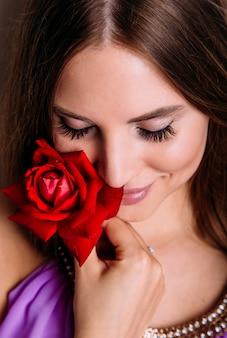 Retrato do close-up da bela modelo mulher com uma rosa vermelha na mão.