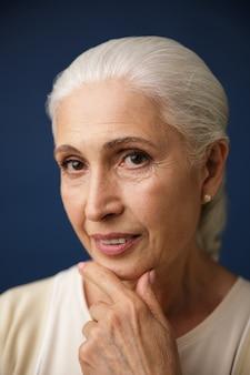 Retrato do close-up da bela mulher idosa com cabelos prateados, segurando o queixo