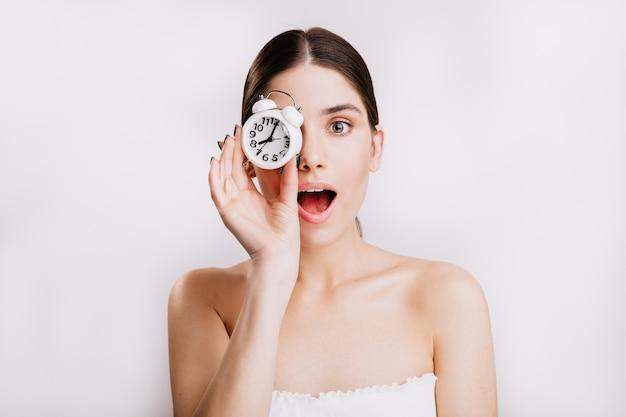 Retrato do close-up da bela senhora com despertador branco cobrindo os olhos dela. sem maquiagem.