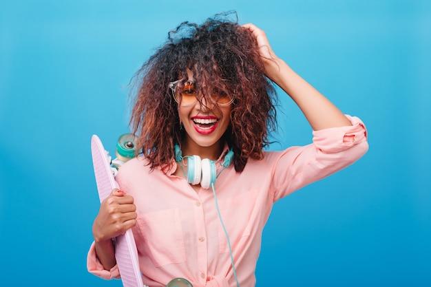 Retrato do close-up da espetacular mulata brinca com o cabelo castanho escuro com longboard. mulher desportiva em fones de ouvido e camisa da moda de algodão, sorrindo na frente da parede azul.