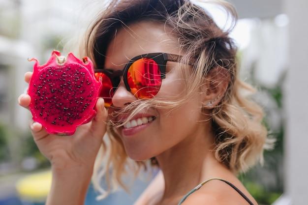 Retrato do close-up da feliz modelo feminina caucasiana de óculos cor de rosa durante a sessão de fotos no resort. mulher branca sorridente com fruta vermelha do dragão