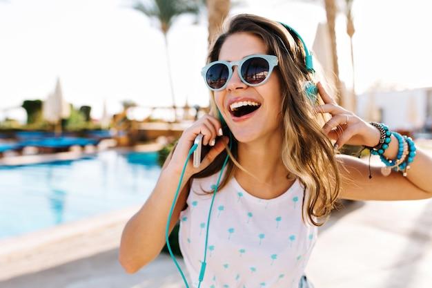 Retrato do close-up da garota bronzeada encaracolada animada em óculos de sol da moda, caminhando à beira da piscina do lado de fora.