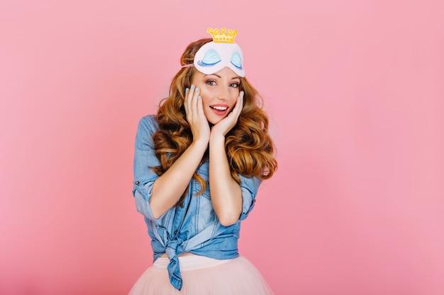 Retrato do close-up da graciosa menina encaracolada na máscara de dormir e camisa jeans retrô, posando com as mãos tocando o rosto. linda garota de cabelos compridos em uma roupa elegante em pé com expressão facial surpresa