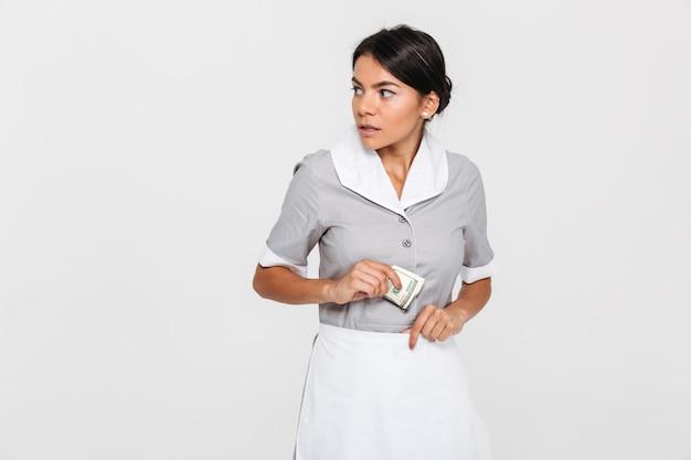 Retrato do close-up da jovem empregada em causa, de uniforme, escondendo as notas de dólar em seu avental, olhando de lado