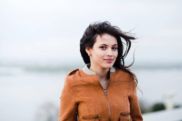 Retrato do close-up da jovem mulher atraente bonita feliz vestindo casaco de couro, sorrindo e em pé