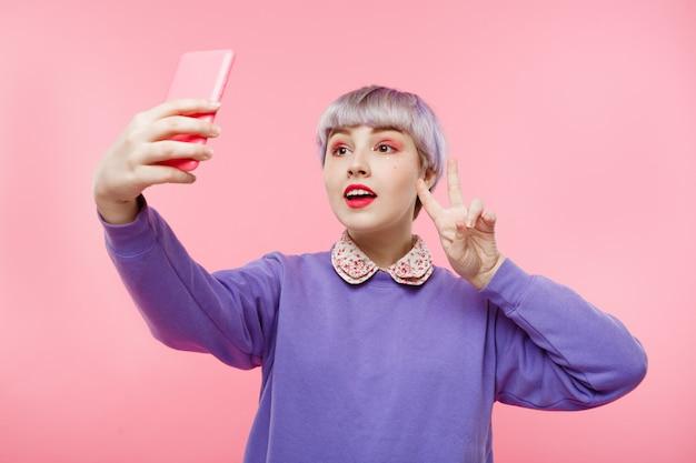 Retrato do close-up da linda garota dollish com cabelo violeta curto curto, vestindo blusa lilás fazendo selfie sobre parede rosa