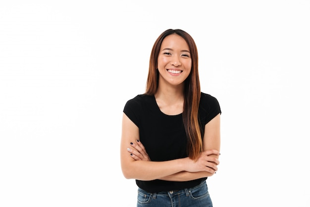 Retrato do close-up da menina asiática nova de sorriso que está com as mãos cruzadas, olhando a câmera