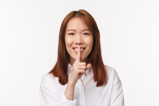 Retrato do close-up da menina asiática tipo gentil pedindo silêncio, mantenha o segredo seguro, sorrindo alegremente e pressione o dedo indicador aos lábios, procurando fazer promessa, silêncio, de pé em uma parede branca