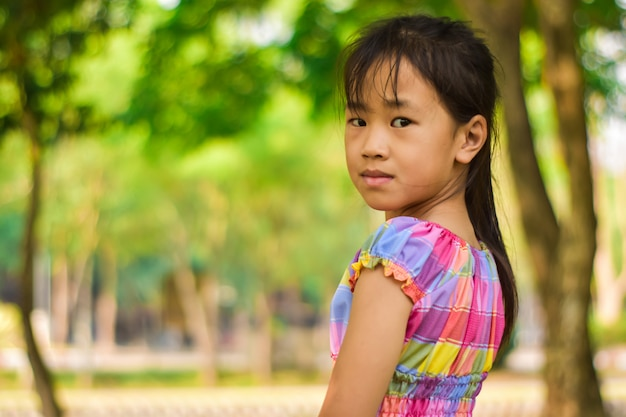 Retrato do close-up da menina bonita em um parque do verde do verão.