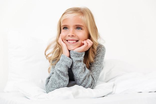 Retrato do close-up da menina bonitinha segurando sua cabeça, olhando asode enquanto estava deitado na cama