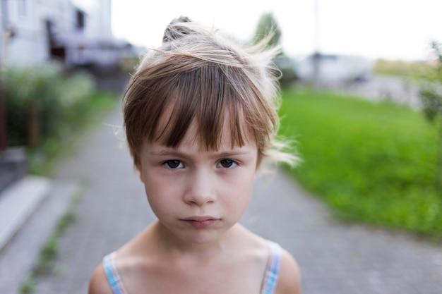 Retrato do close-up da menina consideravelmente nova loura pálida infeliz temperamental criança sem amigos