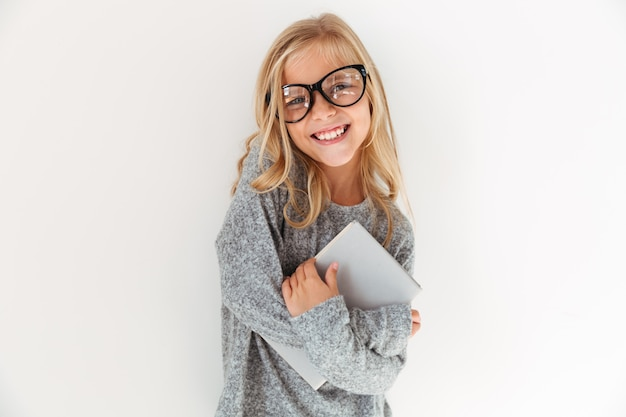 Retrato do close-up da menina feliz em copos, abraçando um livro