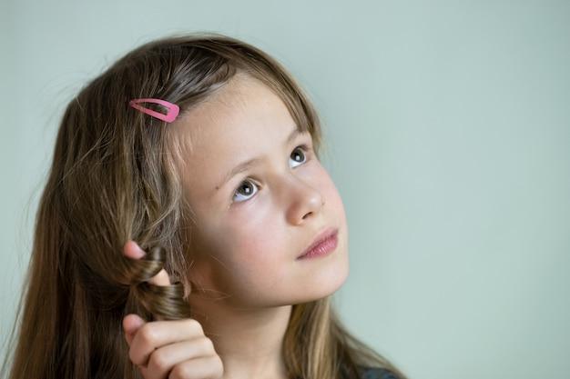 Retrato do close-up da menina sorridente feliz com cabelos longos.
